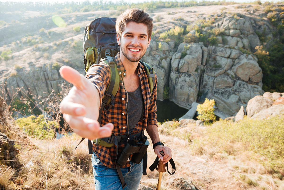 Man takes the hand near the canyon